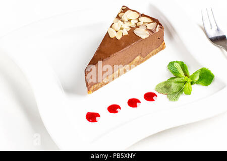 The piece of chocolate souffle cake with mint and jam drops on white plate - Stock Photo