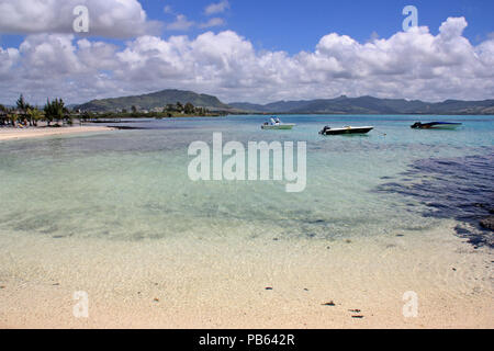 Motorboats anchored at a lagoon with shallow, turquois, crystal clear water in front of a beautiful beach at Mauritius - Stock Photo