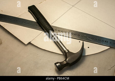 Hammer, metal ruler and cardboard cuts as tools in workshop production of leather goods - Stock Photo