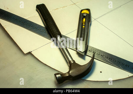 Hammer, metal ruler, cutter knife and cardboard cuts as tools in workshop production of leather goods - Stock Photo