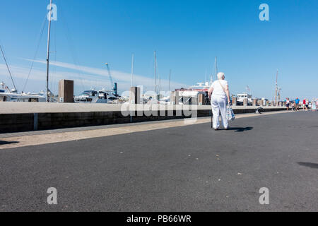 An elderly woman with a walking stick walking along Poole Quay on a sunny summers morning, Poole, Dorset, United Kingdom - Stock Photo