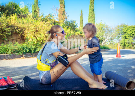 Beautiful sportive mother doing excercises in the park on the mat with her cute little son, the family enjoys sports together, happy healthy lifestyle - Stock Photo