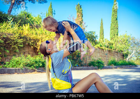 Family enjoying sports together, beautiful sportive mother doing excercises in the park on the mat with her cute little son, lifting her precious baby - Stock Photo