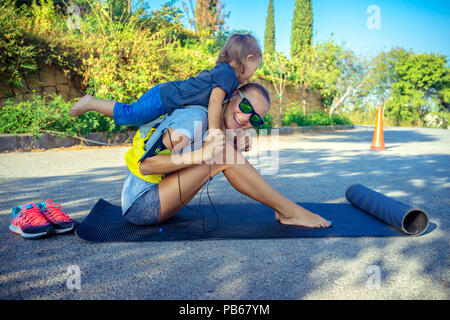 Healthy family life, cute cheerful baby boy plays piggy back and helps her to do stretching, beautiful woman with her little son doing sport excercise - Stock Photo