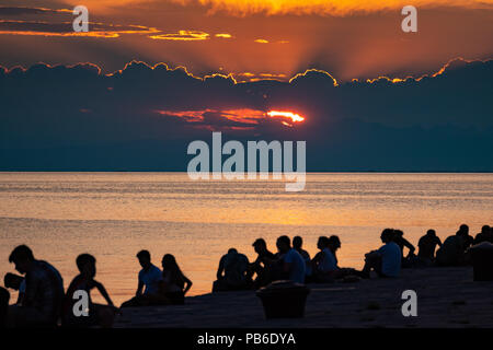 Trieste, Italy, 26 July 2018.  People enjoy the sunset from the iconic  Molo Audace (Audace Pier) in the northern Italy city of Trieste.  The 246-mete - Stock Photo