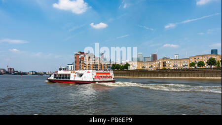 City cruises sightseeing boat 'Millenium Dawn' takes passengers along the River Thames past the Isle of Dogs; Canary Wharf in background. - Stock Photo