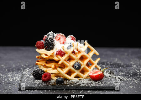 Photo of viennese wafers with fresh raspberries, strawberries sprinkled with powdered sugar on blackboard against blank background - Stock Photo