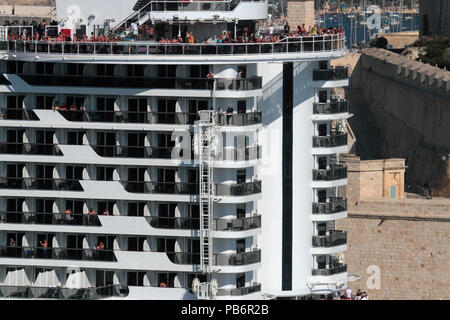 People on the stern of the cruise ship MSC Seaview while departing from Malta. Nine levels are visible, illustrating the size of modern cruise liners. - Stock Photo