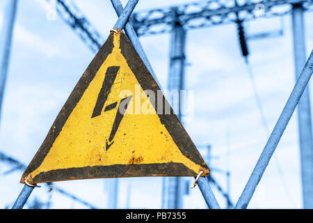 Old aged rusty triangle metal plate with High voltage warning sign. Power station with transformers and electricity distribution lines. Keep out - Stock Photo