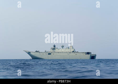 180723-N-VR594-1160 PACIFIC OCEAN (July 23, 2018) Royal Australian Navy landing helicopter dock ship HMAS Adelaide (L01) transits the Pacific Ocean during the Rim of the Pacific (RIMPAC) exercise, July 23. Twenty-five nations, 46 ships, five submarines, and about 200 aircraft and 25,000 personnel are participating in RIMPAC from June 27 to Aug. 2 in and around the Hawaiian Islands and Southern California. The world's largest international maritime exercise, RIMPAC provides a unique training opportunity while fostering and sustaining cooperative relationships among participants critical to ensu - Stock Photo