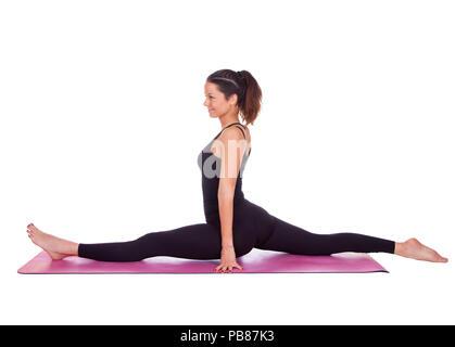 beautiful woman doing hanumanasana pose on yoga class