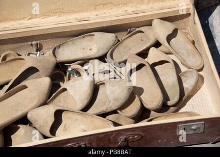 A French Brocante: a suitcase full of wooden clogs - Stock Photo