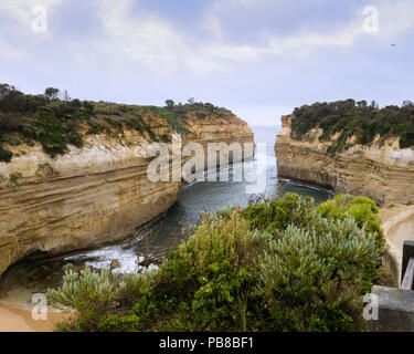 Loch Ard Gorge lookout with old airplane flying by in the distance, Port Campbell National Park, Great Ocean Road, Victoria, Australia - Stock Photo
