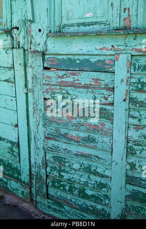 Rustic worn, chipped and weathered old wooden green door - Stock Photo