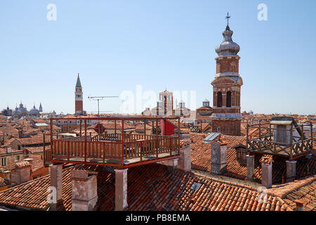 Elevated view of Venice roofs with typical altana balcony and San Marco bell tower in summer, Italy - Stock Photo