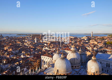 Elevated view of Venice with basilica domes and rooftops from San Marco bell tower before sunset, Italy - Stock Photo