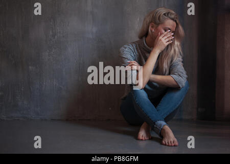 Sad woman. blonde girl sitting on the floor, sadness and depression, concept of psychological problem - Stock Photo