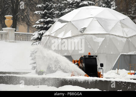 The snow-removing machine clears the city street from snow. snow blower - Stock Photo