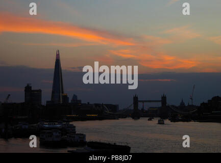 London, UK. 26th July 2018. A layer of what appears to be pollution and haze is seen on the River Thames in London as the sun sets behind Tower Bridge after what was the hottest day of the year so far. Air quality warnings have been issued in the capital. Credit: Vickie Flores/Alamy Live News - Stock Photo