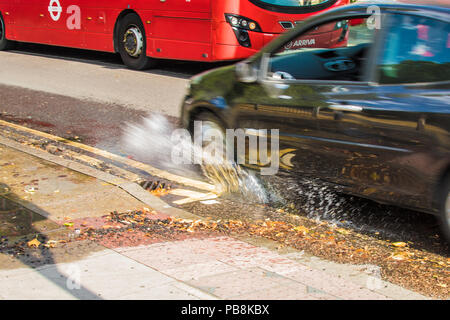 London,UK. 26 July,2018. A car splashes through a pothole caused by leaking water, continuous traffice starts the erosion process and the hole  gets bigger by the day. After being fined £120 million only a month ago by the water regulator OFWAT, Thames Water is still struggling to stay on top of it's leaking, aging pipes.David Rowe/ Alamy Live News - Stock Photo