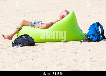 Bournemouth, Dorset, UK. 27th July 2018. UK weather: Sunseekers head to the seaside to soak up the sun at Bournemouth beaches on a warm humid day with some cloud cover. Credit: Carolyn Jenkins/Alamy Live News - Stock Photo