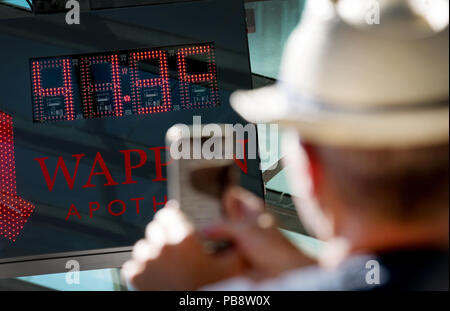 Duesseldorf, Germany. 27th July, 2018. A man photographs the display on a thermometer in downtown Düsseldorf. At 15.30 the display shows 41.3 degrees. Credit: Martin Gerten/dpa/Alamy Live News - Stock Photo