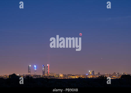 Madrid, Spain. 27th July, 2018. The moon appears near the Four Towers skyscrapers during a total lunar eclipse eclipse, the longest of the century, with a duration of 1 hour 43 minutes and 35 seconds. In Madrid, Spain. Credit: Marcos del Mazo/Alamy Live News - Stock Photo