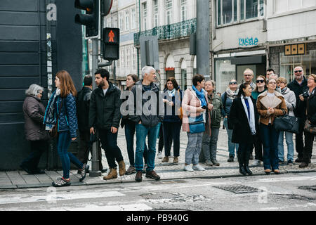 Portugal, Porto, May 05, 2018: A crowd of people stands on a red traffic light and wait for the green light to turn to cross the street. - Stock Photo