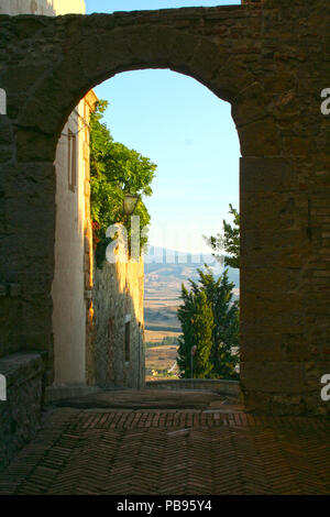 Tuscan countryside viewed through an archway in Pienza, Tuscany, Italy - Stock Photo