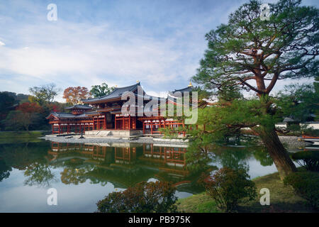 Beautiful Amida hall of Byodo-in temple on the pond of Jodo-shiki Pure Land garden in early morning sunrise scenery with bright blue sky. Uji, Kyoto P - Stock Photo