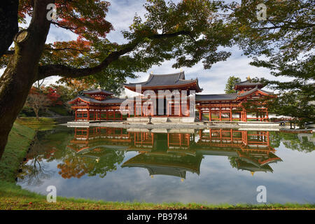 Peaceful autumn scenery of the Phoenix Hall, Amida hall of Byodoin temple on Kojima island of Jodoshiki teien, Pure Land garden pond on a bright sunny - Stock Photo