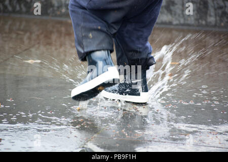 Close-up of kid wearing blue rain boots and walking during sleet, rain and snow on cold day. Child in colorful fashion casual clothes jumping in a pud - Stock Photo