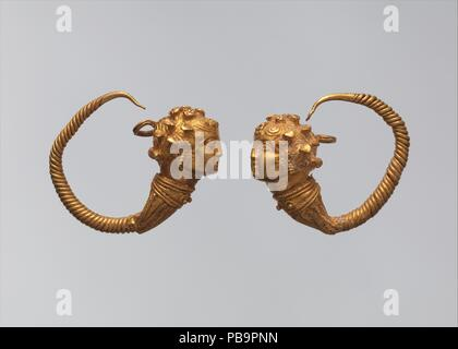 Maenad-head earrings. Dimensions: a. As Worn: H. 2.5 × W. 2.9 cm (1 × 1 1/8 in.)  b. As Worn: H. 2.4 × W. 2.7 cm (15/16 × 1 1/16 in.). Date: 1st century B.C..  Earrings with heads of maenads (Dionysus's female followers) are rare in Egypt but occur in the Levant and Cyprus. The form is late Hellenistic. Museum: Metropolitan Museum of Art, New York, USA. - Stock Photo