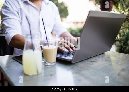 Young attractive afro American businessman sitting in cafe bar, drinking coffee and doing some work on laptop. - Stock Photo