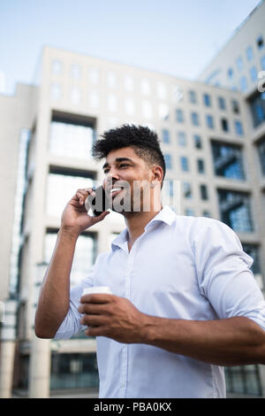 Young handsome Afro American man standing in front of huge modern business building, smiling, holding coffee to go and talking on mobile phone. - Stock Photo