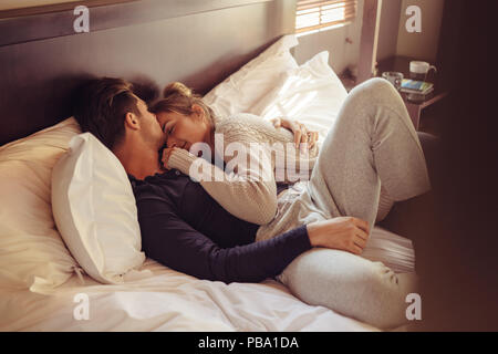 Loving young couple sleeping together in bed. Young man and woman lying together in bedroom. - Stock Photo