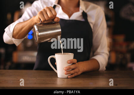 Woman wearing apron pouring milk into a cup of coffee, making espresso. Professional barista preparing coffee on cafe counter. - Stock Photo