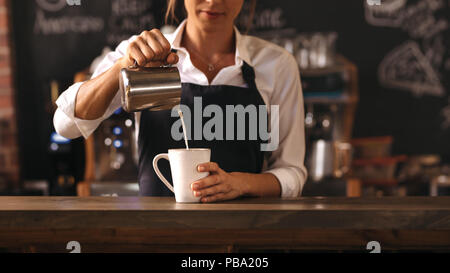 Cropped shot of female barista making a cup of coffee while standing behind cafe counter. Young woman pouring milk into a cup of coffee. - Stock Photo
