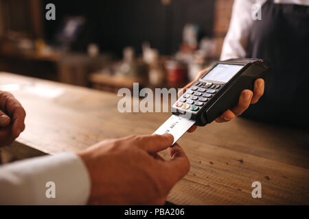 Customer inserting his credit card in the machine to payment at cafe. Customer paying for their order with a credit card in a cafe, with bartender hol - Stock Photo