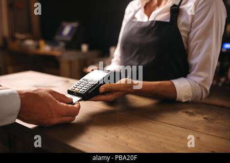 Female bartender holding a credit card reader machine with male customer inserting the card in machine for payment. - Stock Photo