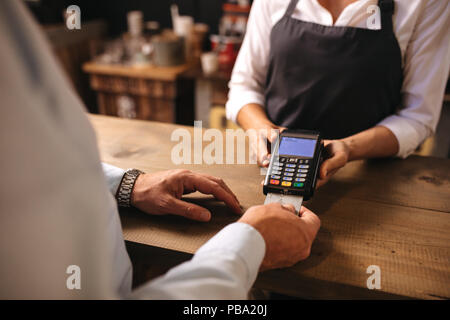 Cropped shot of male customer paying for coffee by credit card at cafe. Woman barista holding a credit card reader machine with man doing payment on c - Stock Photo