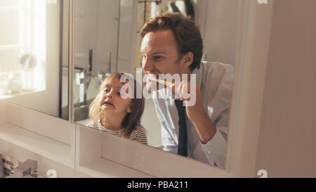 Man brushing his teeth looking into the mirror standing in bathroom while his daughter looks on. Man teaching his daughter how to brush teeth. - Stock Photo