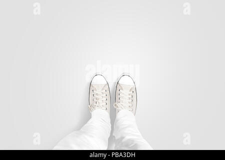 Person taking photo of his foots stand on blank floor, isolated, top view, clipping path. Ground design mock up. Man wear gumshoes and watching down.  - Stock Photo