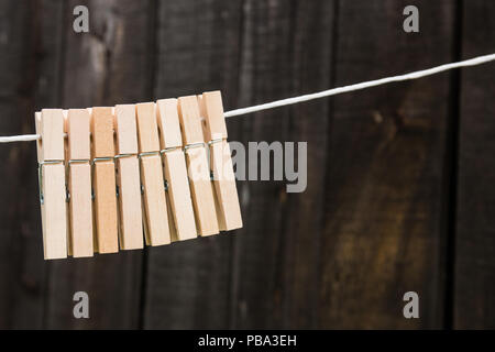 wooden clothespins hang on a rope on a wooden background - Stock Photo
