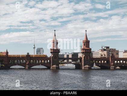 old red bridge with two towers, Oberbaum bridge, over Spree river in Berlin with a yellow train tram going over. - Stock Photo
