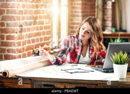 Pretty ambitious female architect in plaid shirt drawing a new project in loft office - Stock Photo