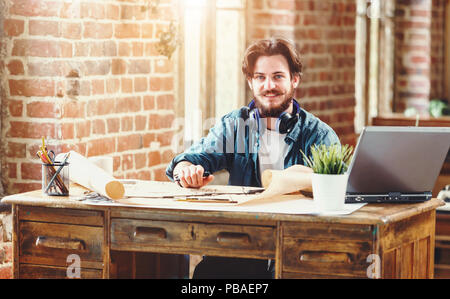 Handsome bearded male architect working on a building plan at his desk smiling to the camera joyfully copyspace professionalism trustworthy qualified experienced engineer constructionist developer - Stock Photo