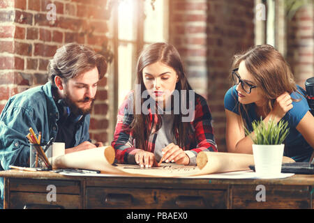 Crew of young professional designers discussing ideas about blueprint during meeting in the loft modern office - Stock Photo