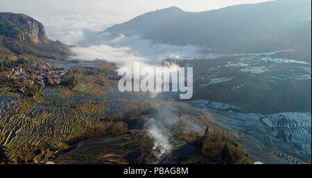 Aerial view on water-filled rice terraces and a valley covered by fog. Yuanyang Rice Terraces early in the morning during spring. - Stock Photo