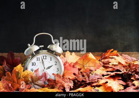 Alarm clock in colorful autumn leaves against a dark background with shallow depth of field. Daylight savings time concept. - Stock Photo